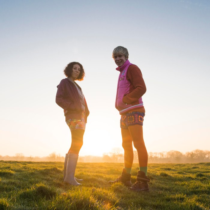 Billy Bottle and Martine stood in a field in front of a sunset